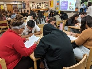students peer editing essays at tables in the school library